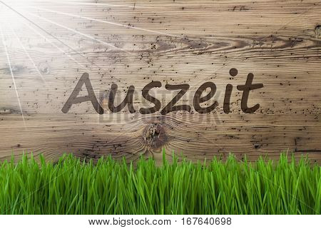German Text Auszeit Means Downtime. Spring Season Greeting Card. Sunny Aged Wooden Background With Gras.