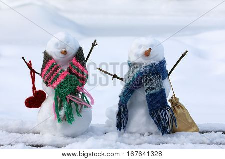 two smile snowmen in scarves against the background of the snow drifts / fun walk together