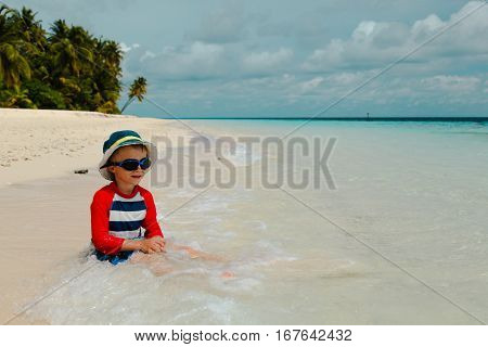 happy little boy relaxed in water at tropical beach