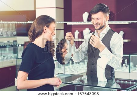 Jeweler brunette man with beard holding and showing golden necklace with blue stones for buyer. Looking each other and smiling. Happy brunette girl with long hair choosing jewelry in luxury store.