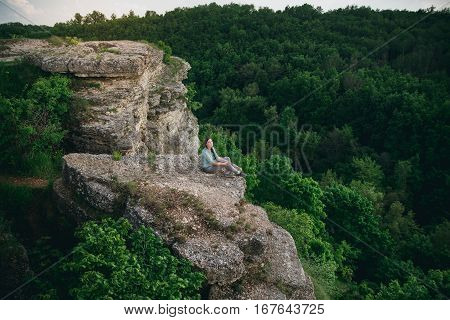 Tourist girl sitting on a rock background of green forest