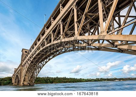 View of Britannia bridge across Menai Strait between island of Anglesey and mainland of Wales. Copy space in sky. poster