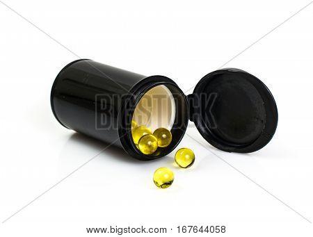 Small round yellow gelatin capsules in black jar on white