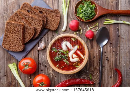 Beet soup in wooden plate with vegetables on wooden table. Borch, traditional Russian food