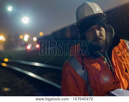 Portrait of young construction worker in helmet at night