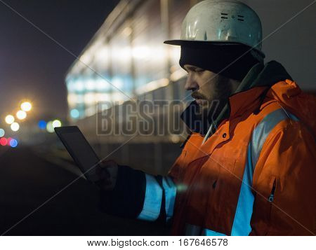 Portrait of young engineer working during hignt otdoors in helmet and reflective