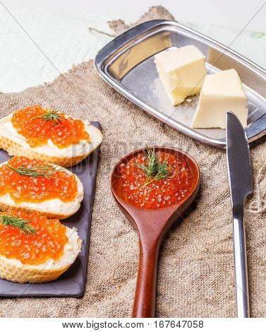 Sandwiches with red roe, wooden spoon, butter knife on white wooden table