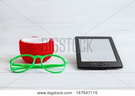 E-book glasses and a cup of tea on a white background. The concept of modern technology and reading.