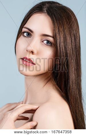 Young beautiful woman with healty fresh skin looking around over blue background. Spa concept.