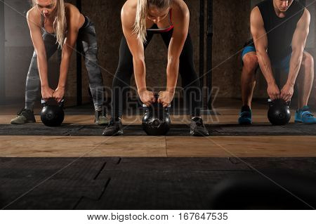 Group of muscular adults doing exercises with kettle bell in gym. Weightlifting, power lifting workout. fitness, sports concept.
