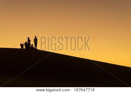 Family on the silhouette while picnic on the park