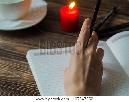Close up of female hands writing with pencil at cafe with burning candle.