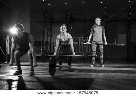 Young muscular adults exercising with barbells in gym. Three athletes doing dead lift with weights. Fitness, sports concept. Selective focus.