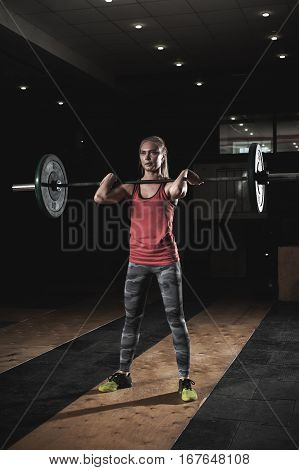 Cute blonde girl lifting barbell with weights. Young strong woman doing weightlifting workout in gym. Fitness, sports concept.