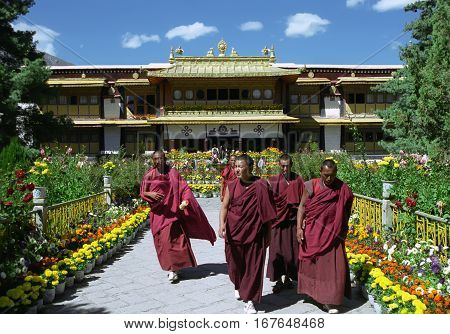 Lhasa, Tibet, China - September 2007: Buddhist monks go from excursion of the summer residence of Dalai Lama - Norbulingka on September 2007 in Lhasa, Tibet, China.