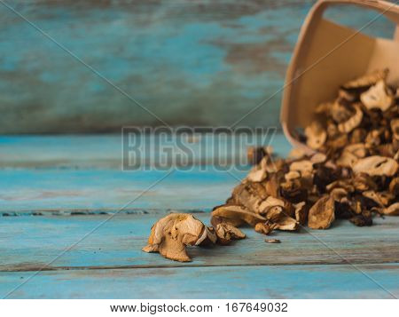 Dried Mushrooms in basket closeup on blue Wooden background