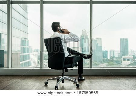 Rear view of businessman talking on phone while sitting down in an office with panoramic city view