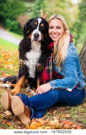 Woman cuddling with dog outside in park