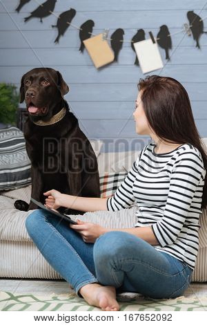 What a good boy. Elegant attentive joyful woman talking to her nice Labrador while sitting in front of him on the floor and holding a tablet in her hands