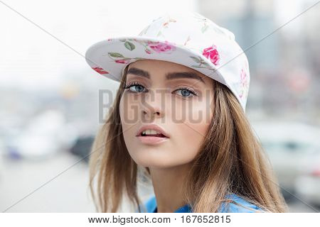 Closeup Portrait of a beautiful girl in a baseball cap posing outdoors