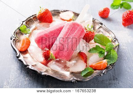 Homemade strawberry popsicles on metal plate with ice and berries. Summer food concept.