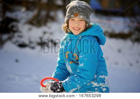 Winter portrait of the boy of younger school age. The nice fellow in a blue jacket and a gray knitted cap joyfully smiles. He rejoices to snow. Snow on clothes and the boy's hair.