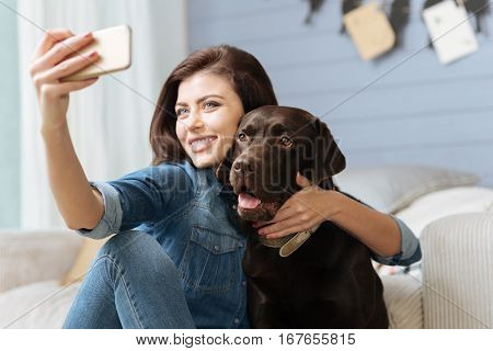 Pose like a model. Enthusiastic cheerful pretty lady taking a picture of herself hugging her nice dog while spending time in a bright blue living room