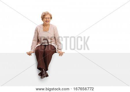 Joyful mature woman sitting on a panel isolated on white background