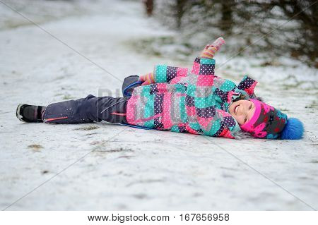The girl of younger school age has moved down from a hill on the sledge and lies on snow. To the girl it is very cheerful. She is dressed in a warm bright ski suit and a cap.