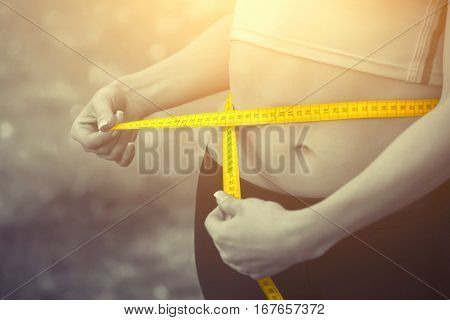 Sport girl measuring waist with yellow measuring tape. Reducing excess weight. Healthy lifestyle.