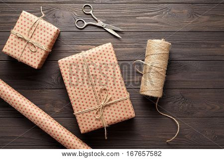 Box with a gift, wrapping paper, scissors, twine. table ideas for wrapping gifts for birthdays and holidays. Rustic style and dark wood background. Flat lay.