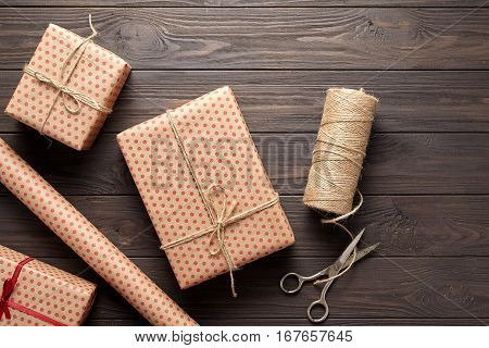 The concept of wrapping gifts in rustic style on birthday or holidays. Wrapping paper, scissors, twine. Dark wooden background. Flat lay. View from above.