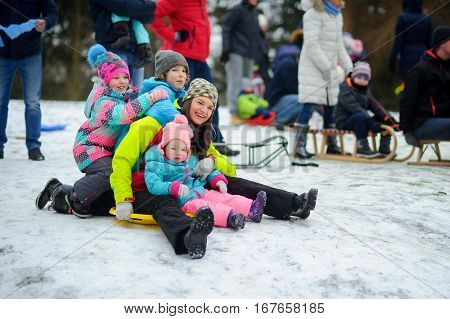 Merry sledging from the hill. At the top of hills crowded. The young woman and three children in one sledge prepares for descent. Such winter entertainments are loved by both adults and children.