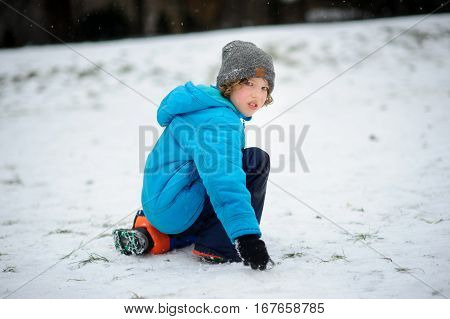 The boy in a blue jacket alone sits on snow. On his face pain offense tears. Something has upset the child. Winter entertainments not always only please.