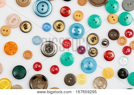 Close-up Shot Of Many Different Buttons On A White Background, Flat Lay Pattern.