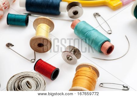 Spools Of Thread, Needles And Other Sewing Stuff On A White Background, Close-up Shot
