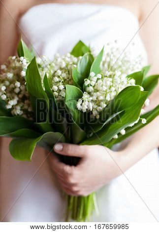 Bouquet of fresh lilies of the valley in the hands of a young woman in a white dress. Close up. The symbol of the coming of spring and warmth.