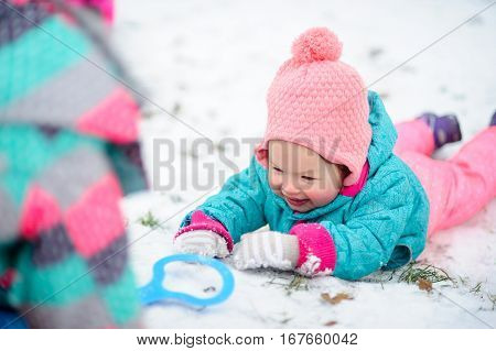 The little girl lies on snow and smiles. Snow gives the child joy. Someone was inclined over the baby. Children like winter games.