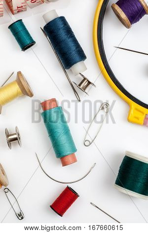 Spools Of Thread, Needles And Other Sewing Stuff On A White Background, Close-up Shot, Vertical