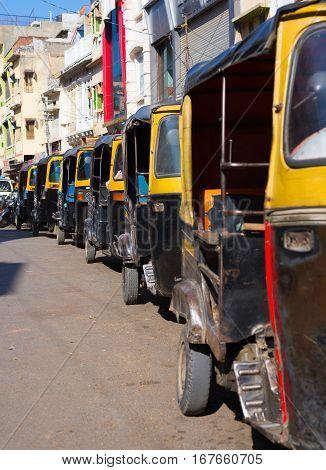 Yellow black rickshaws (tuk tuk) lined up in the street of Udaipur Rajasthan India.
