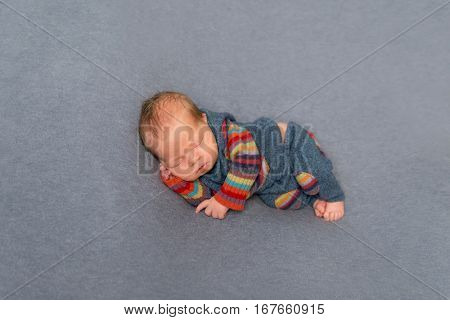 Sweet hairy newborn napping on his side, in striped pants and jacket