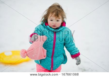 Winter portrait of the little girl. Baby in a bright ski suit. Her became hot from a game and she has taken off from herself a cap. Child has rosy cheeks and the tousled hair.