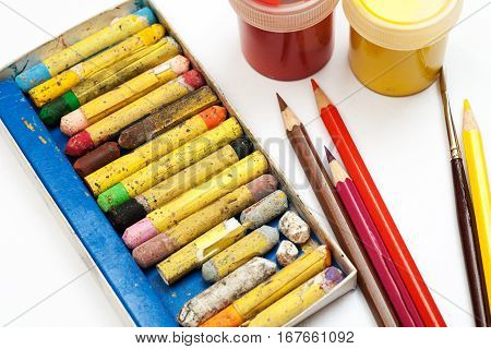 Crayons, Pencils, Brushes And Gouache Jars On A White Background