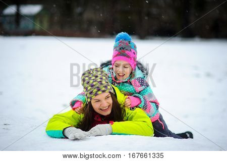 Lovely young woman and girl in bright jackets lie on snow. It is snowing. Mother and the daughter cheerfully flounder in snow. Snow is loved by both adults and children.