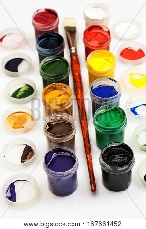 Many Open Jars With Paint And Brush Among Them On A White Background, Angle View, Vertical