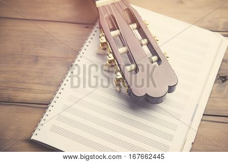 guitar with notepad on the  wood table