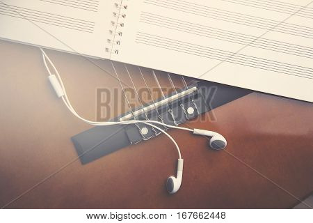 guitar with notepad and earphone on wood table