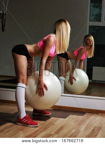 Sports blonde girl doing warm up in the gym with white ball near a mirror