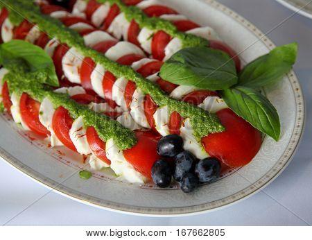Caprese salad with tomatomozzarella bazil and pesto on a dish. Selective focus