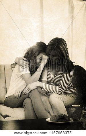 Grey background against mother comforting daughter